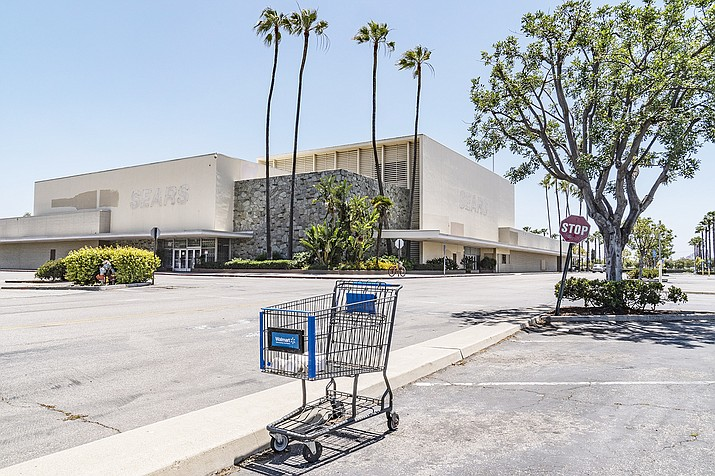 This Thursday, May 27, 2021, photo shows an empty shopping cart in an empty parking lot at the closed Sears in Buena Park Mall in Buena Park, Calif. California state lawmakers are grappling with a particularly 21st-century problem: What to do with the growing number of shopping malls and big-box retail stores left empty by consumers shifting their purchases to the web. A possible answer in crowded California cities is to build housing on these sites, which already have ample parking and are close to existing neighborhoods. Even before the pandemic, big-box retail stores struggled to adapt as more people began buying things online. In 2019, after purchasing Sears and Kmart, Transformco closed 96 stores across the country, 29 in California. (Damian Dovarganes/AP)