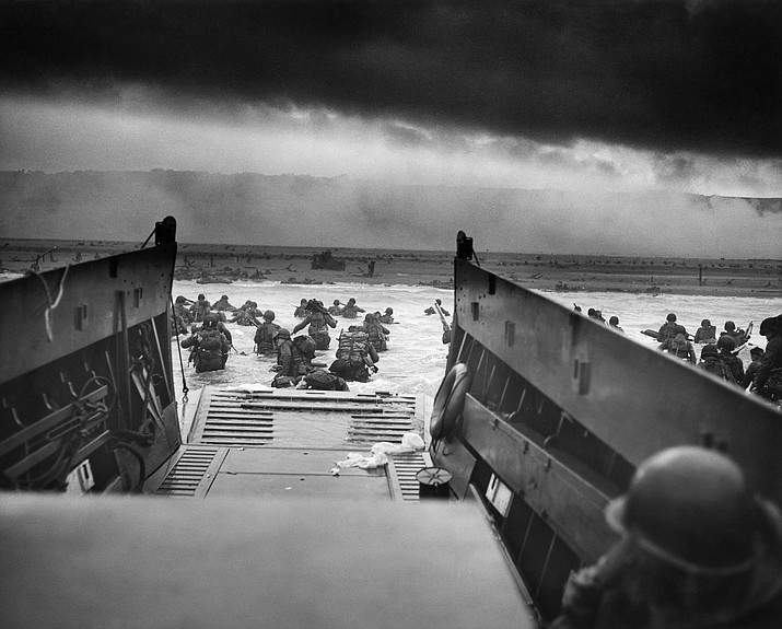 A LCVP (Landing Craft, Vehicle, Personnel) from the U.S. Coast Guard-manned USS Samuel Chase disembarks troops of Company E, 16th Infantry, 1st Infantry Division wading onto the Fox Green section of Omaha Beach on the morning of June 6, 1944. American soldiers encountered the newly formed German 352nd Division when landing. During the initial landing two-thirds of Company E became casualties. (Chief Photographer's Mate Robert F. Sargent, file)
