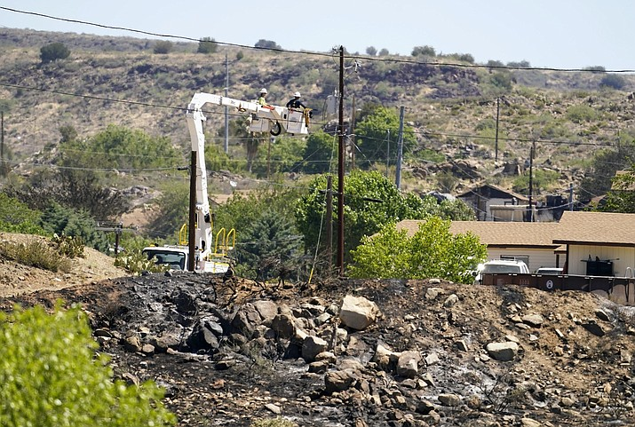 An Arizona Public Service crew works to restore power to Bagdad May 28. The Spur Fire, which burned 150 acres and destroyed 24 homes and other structures May 27-28, 2021, in Bagdad, Arizona, has been deemed an accident. (Rob Schumacher/The Arizona Republic via AP, Pool)