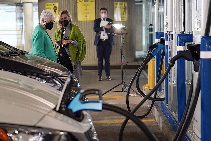 In this Thursday, April 22, 2021 file photo, White House climate adviser Gina McCarthy, left, talks with EVgo Chief Executive Officer Cathy Zoi, before the start of an event near an EVgo electric car charging station at Union Station in Washington. If the auto industry is to succeed in its bet that electric vehicles will soon dominate the roads, it will need to overcome a big reason why many people are still avoiding them: Fear of running out of juice between Point A and Point B. (Susan Walsh/AP)