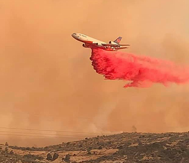 An airplane drops slurry near the community of Miami, Arizona, as evacuations were underway due to a wildfire Monday, June 7, 2021. (Gila County Sheriff's Office, Facebook/Courtesy)