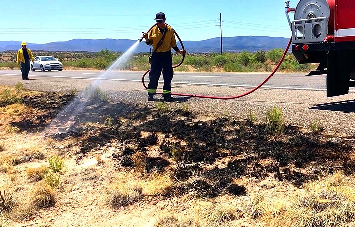 Firefighters mop up a small brush fire on State Route 260, east of Cottonwood late Saturday morning. VVN/Vyto Starinskas
