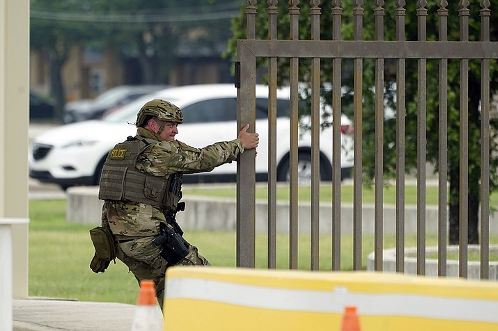 A military policeman closes a gate at JBSA-Lackland Air Force Base, Wednesday, June 9, 2021, in San Antonio. The Air Force was put on lockdown as police and military officials say they searched for two people suspected of shooting into the base from outside. (Eric Gay/AP)