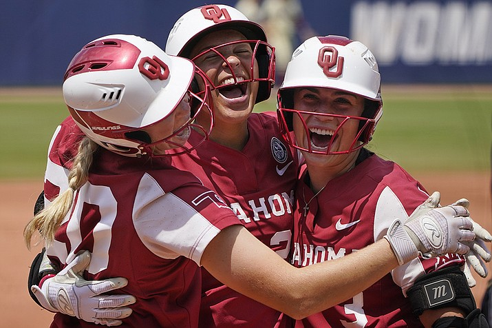 Oklahoma's Jayda Coleman, center, celebrates at home plate with teammates Jana Johns, left, and Grace Lyons, right, following her home run against Florida State in the second inning of the final game of the NCAA Women's College World Series softball championship series Thursday, June 10, 2021, in Oklahoma City. ( Sue Ogrocki/AP)