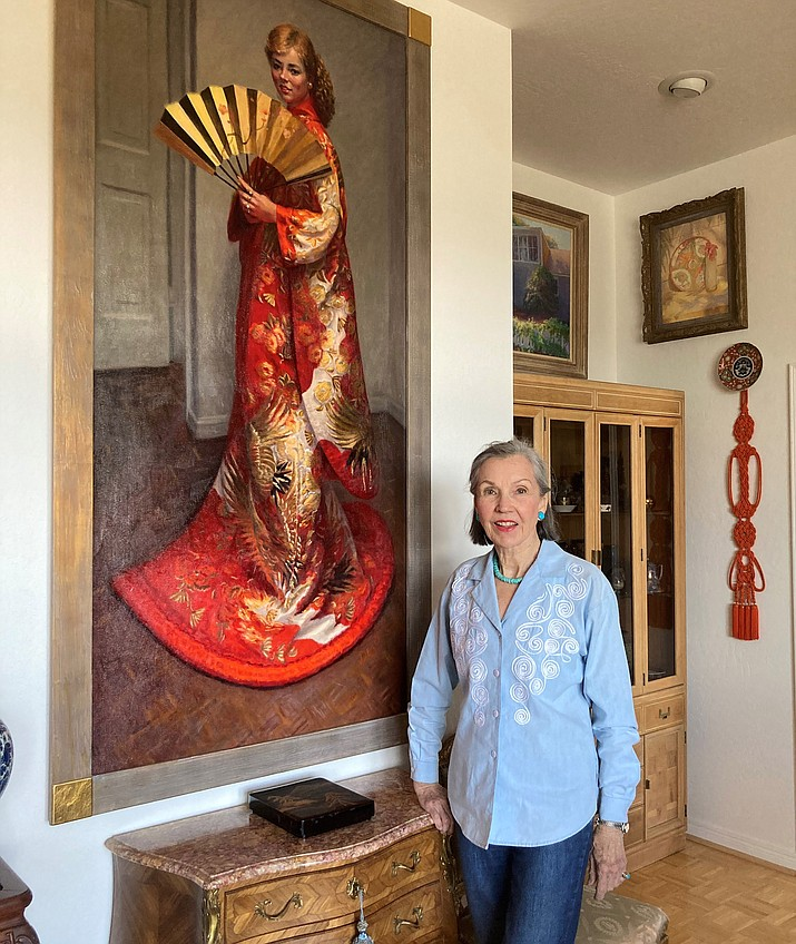 Dezie Lerner stands before a large-sized living room portrait of her niece, Helen Kelly, dressed in a bright red kimono Dezie purchased from Japan for the portrait. (Nanci Hutson/Courier)