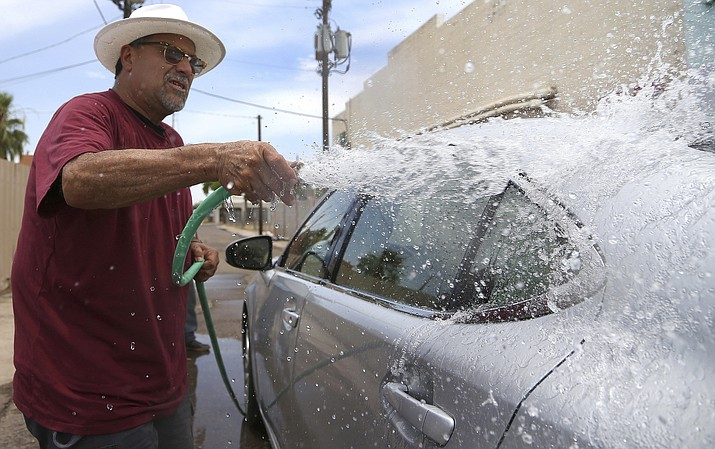 Justa Center extended care manager Rudy Soliz rinses off a car at a car wash to raise money for the at-risk senior homeless facility July 12, 2019, in Phoenix. The warning issued by the National Weather Service for high temperatures of up to 118 degrees for desert areas of south-central Arizona is set begin Saturday, June 12, 2021, and extend to next Friday.(Ross D. Franklin/AP,file)
