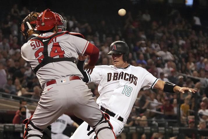 Arizona Diamondbacks' Carson Kelly (18) scores under the tag of Los Angeles Angels catcher Kurt Suzuki during the sixth inning of a baseball game Friday, June 11, 2021, in Phoenix. (Rick Scuteri/AP)