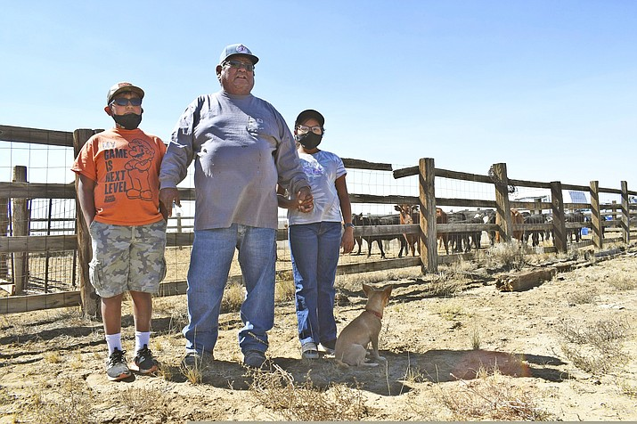 Navajo rancher Timothy Largo and his grandchildren stand outside a corral at the Sims Ranch near Crownpoint, New Mexico. Navajo ranchers impacted by the pandemic and ongoing drought may soon qualify for assistance to supplement their livestock with hay and grain. (Vida Volkert/Gallup Independent via AP)