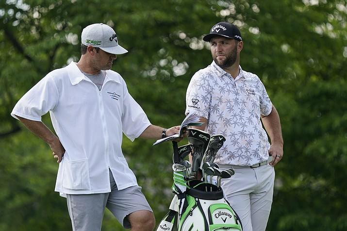 Jon Rahm talks with his caddie as he waits to hit on the 14th tee during the third round of the Memorial golf tournament, Saturday, June 5, 2021, in Dublin, Ohio. Rahm was later notified he tested positive for the coronavirus, knocking him out of the tournament. (Darron Cummings/AP)