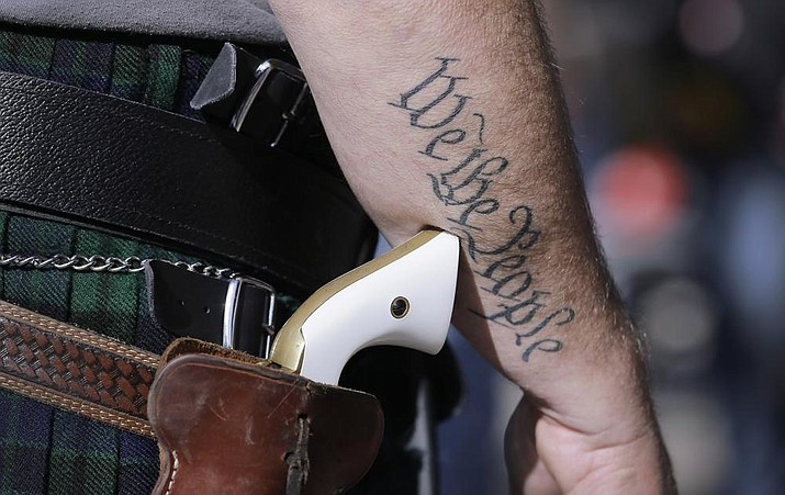 In this file photo, a supporter of open carry gun laws, wears a pistol as he prepares for a rally in support of open carry gun laws at the Capitol, in Austin, Texas. Texas lawmakers have given final approval to allowing people carry handguns without a license, and the background check and training that go with it. The Republican-dominated Legislature approved the measure Monday, May 24, 2021 sending it to Gov. Abbott. (AP Photo/Eric Gay, File)