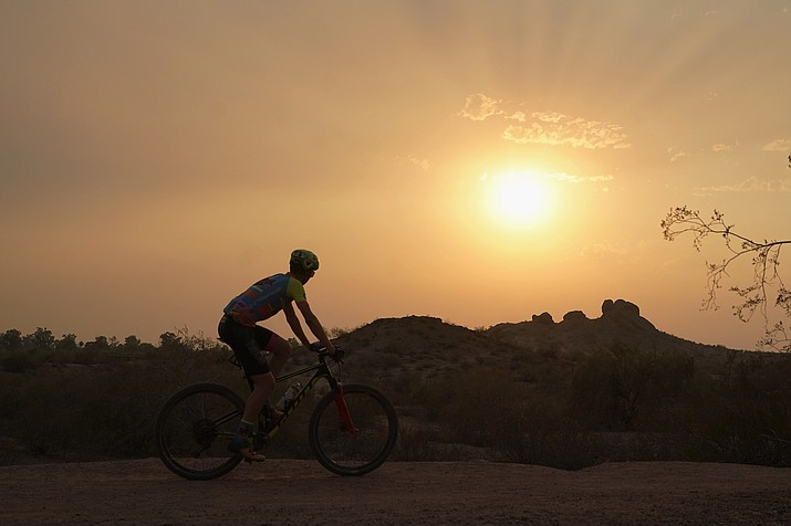 A cyclist bikes past the setting sun at Papago Park during a heatwave where temperatures hit 115-degrees Tuesday, June 15, 2021, in Phoenix. (Ross D. Franklin/AP)