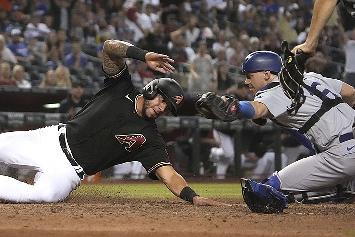 Arizona Diamondbacks' David Peralta, left, avoids the tag by Los Angeles Dodgers catcher Will Smith to score during the eighth inning of a baseball game Saturday, June 19, 2021, in Phoenix. (Rick Scuteri/AP)