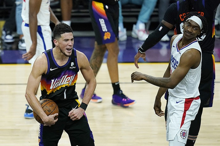 Phoenix Suns guard Devin Booker (1) celebrates near the end of the second half of Game 1 of the NBA basketball Western Conference finals as Los Angeles Clippers guard Terance Mann, right, looks on Sunday, June 20, 2021, in Phoenix. (Ross D. Franklin/AP)