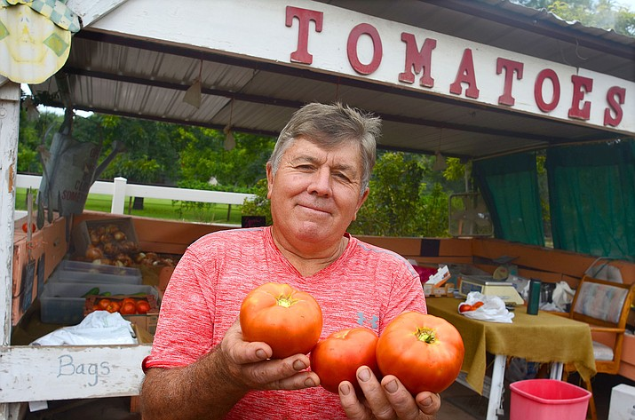 David Stutzman holds some of his fire-engine red tomatoes at this Camp Verde tomatoes stand in 2019. He passed away on Tuesday, according to the Peoria Fire Department where he was a captain. VVN/Vyto Starinskas