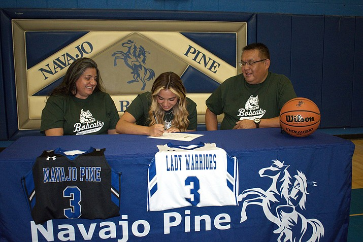 Jordan Louis of Crystal, New Mexico, and recent graduate of Navajo Pine High School, signs a letter of intent to play basketball for Paul Smith's College in New York. She was supported by her parents, Shane and Monique Louis, during the signing ceremony June 12, at NPHS. (Submitted photo)