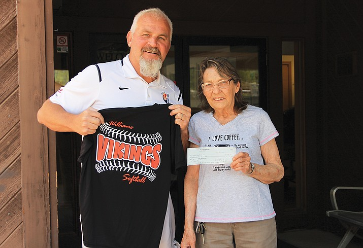 Mary Martin gives a check to Williams High School Athletic Director Phillip Echeverria. The Williams Senior Center Thrift Store donated $500 to the Williams High School softball  team to purchase rings for the 2021 State Champs. Martin said the organization finds it important to support the community's youth.  (Wendy Howell/WGCN)
