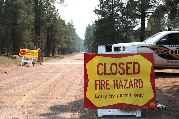 Coconino County Sheriff's Office blocks off a U.S. Forest Service Road outside of Flagstaff June 21. Dozens of wildfires are burning in hot, dry conditions across the U.S. West. (Brady Wheeler/Arizona Daily Sun via AP)