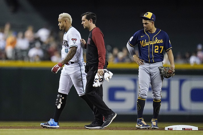 An injured Arizona Diamondbacks' Ketel Marte (4) is helped off the field by Diamondbacks assistant athletic trainer Ryne Eubanks, middle, as Milwaukee Brewers shortstop Willy Adames (27) looks on during the first inning of a baseball game Tuesday, June 22, 2021, in Phoenix. (Ross D. Franklin/AP)
