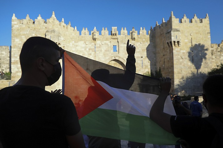 In this June 19, 2021, photo, Palestinians demonstrators wave the Palestinian flag during protest in Damascus gate just outside Jerusalem's Old City. A new poll on U.S. attitudes toward a core conflict in the Middle East finds about half of Democrats want the country to do more to support the Palestinians (Mahmoud Illean/AP, File)