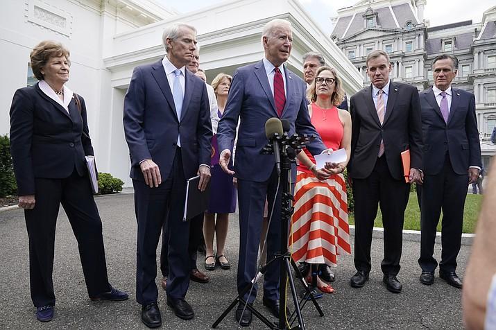 President Joe Biden, with a bipartisan group of senators, speaks Thursday June 24, 2021, outside the White House in Washington. Biden invited members of the group of 21 Republican and Democratic senators to discuss the infrastructure plan. From left are, Sen. Jeanne Shaheen, D-N.H., Sen. Rob Portman, R-Ohio, Sen. Bill Cassidy, R-La., Sen. Lisa Murkowski, R-Alaska, Biden, Sen, Joe Manchin, D-W.Va., Sen. Kyrsten Sinema, D-Ariz, Sen. Mark Warner, D-Va., and Sen. Mitt Romney, R-Utah. (Jacquelyn Martin/AP)