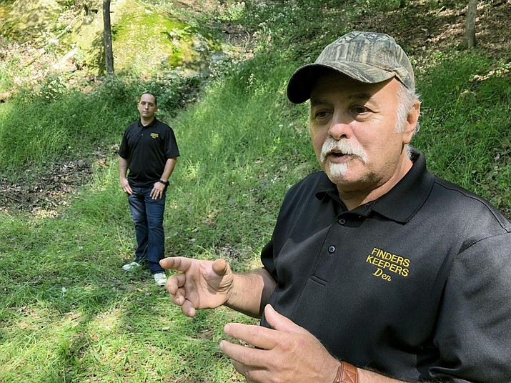 """This Sept. 20, 2018 photo, Dennis Parada, right, and his son Kem Parada stand at the site of the FBI's dig for Civil War-era gold in Dents Run, Pa. Court documents unsealed Thursday, June 24, 2021, show that an FBI agent applied for a federal warrant in 2018 to seize a cache of gold that he said had been """"stolen during the Civil War"""" while en route to the U.S. Mint in Philadelphia. The Paradas, co-owners of the treasure-hunting outfit Finders Keepers, have said they believe the FBI found gold at the site and have pursued legal action to get more information. (AP file)"""