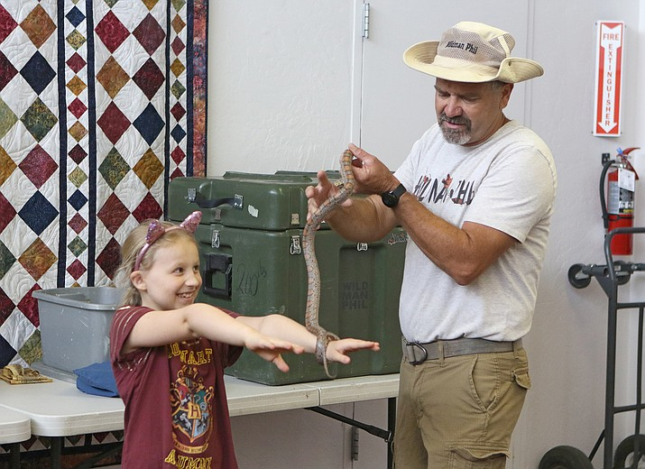 Wildman Phil handles a corn snake and places it on the arms of Luci Arbon during a demonstration event hosted by the Chino Valley Public Library on Wednesday, June 23, 2021. Wildman Phil spoke and displayed a variety of exotic animals, including snakes, alligators, chuckwallas and Gila monsters. The library currently has a summer-fun family event scheduled every Wednesday through July 23. For more information, visit chinoaz.net/214/Library or contact RLaurence@chinoaz.net or 928-636-9115. (Matt Santos/Courtesy)