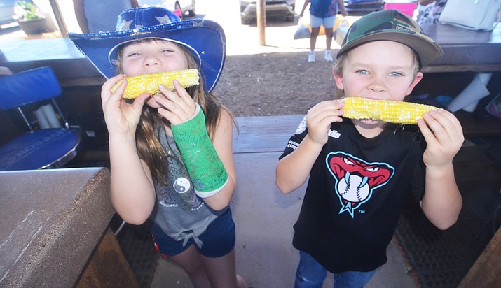 Cy Hauser and Bentleigh Hauser eat some corn on the cob right off the stalk at the Hauser & Hauser Farms on opening day on Monday. VVN/Vyto Starinskas