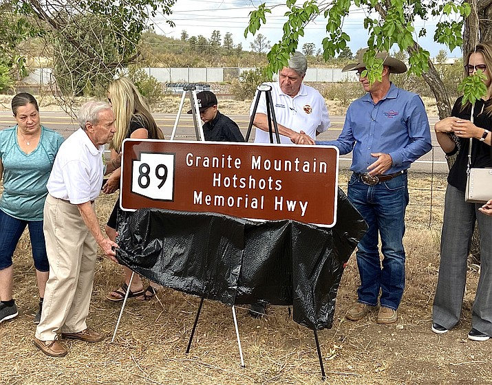Granite Mountain Interagency Hotshot Crew Learning and Tribute Center board member John Marsh unveils the newest memorial Highway 89 sign for the Granite Mountain Hotshots while Prescott Fire Chief Dennis Light and Mayor Greg Mengarelli shake hands during an event Tuesday, June 29, 2021, at Watson Lake. (Aaron Valdez/Courier)