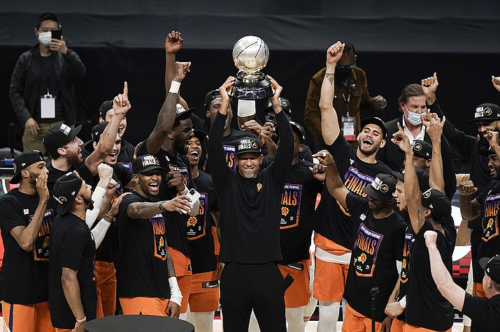 Phoenix Suns head coach Monty Williams, center, hoists the trophy as he and his players celebrate after defeating the Los Angeles Clippers in Game 6 of the NBA basketball Western Conference Finals Wednesday, June 30, 2021, in Los Angeles. (Jae C. Hong/AP)
