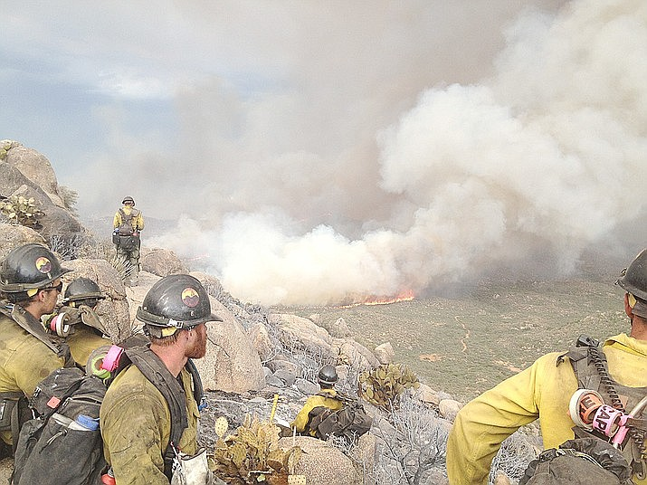 The Granite Mountain Hotshots watch the Yarnell Hill Fire from a burned-out area on June 30, 2013, less than an hour before the wildfire blocked their escape through a valley and overran their position, killing them. (Hotshot Christopher MacKenzie/Courtesy of his family)