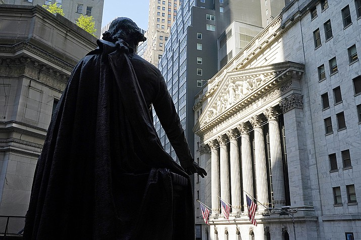 In this June 7, 2021 file photo, the Federal Hall statue of George Washington overlooks the New York Stock Exchange. Wall Street capped a milestone-shattering week Friday with stock indexes hitting more record highs as investors welcomed a report showing the nation's job market was even stronger last month than expected. (Richard Drew, AP File)