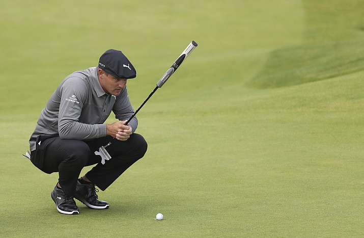 In this July 18, 2019 photo, Bryson DeChambeau, of the United States, looks at his putt on the fourth green during the first round of the British Open Golf Championships at Royal Portrush in Northern Ireland. DeChambeau wasted no time defending himself against accusations of slow play Saturday, Aug. 10, after harsh criticism on social media stemming from a video showing him taking more than two minutes to hit an 8-foot putt at The Northern Trust. (Peter Morrison/AP, File)