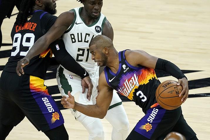 Phoenix Suns guard Chris Paul (3) drives pst Milwaukee Bucks guard Jrue Holiday (21) during the second half of Game 1 of basketball's NBA Finals, Tuesday, July 6, 2021, in Phoenix. (Matt York/AP)