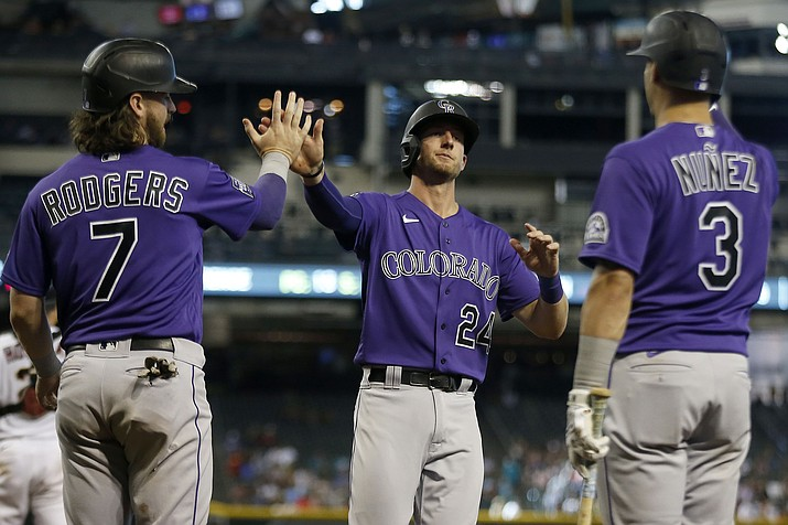 Colorado Rockies' Ryan McMahon (24) is greeted at home plate by Brendan Rodgers (7) and Dom Nuñez (3) after scoring against the Arizona Diamondbacks during the seventh inning of a baseball game Thursday, July 8, 2021, in Phoenix. (Darryl Webb/AP)