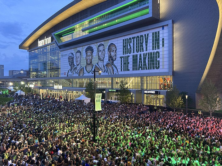 """Thousands of fans gather outside Fiserv Forum to watch on a video screen as the Milwaukee Bucks play at Phoenix in Game 1 of the NBA Finals on Tuesday, July 6, 2021, in Milwaukee. Bucks officials said 9,000 fans watched the game on a video screen inside Fiserv Forum and another 20,000 watched in the """"Deer District"""" outside the arena. The Bucks are in the finals for the first time since 1974 as they chase their first championship since 1971. (Steve Megargee/AP)"""