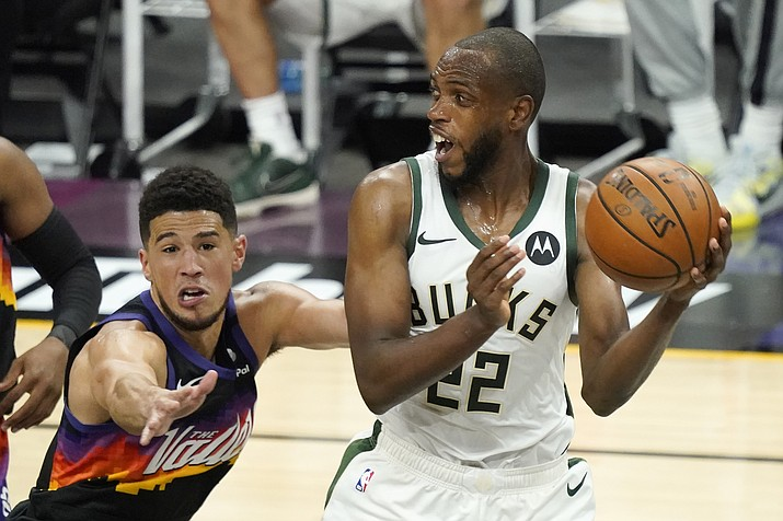 Milwaukee Bucks forward Khris Middleton (22) is defended by Phoenix Suns guard Devin Booker during the second half of Game 2 of basketball's NBA Finals, Thursday, July 8, 2021, in Phoenix. (Matt York/AP)