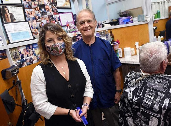 Kathy Moura, left, poses with Pio Imperati at Pio of Italy Hair Studio on Whalley Avenue in New Haven on June 29, 2021. At right is longtime customer Arnie Mann (Hearst Connecticut Media via AP)
