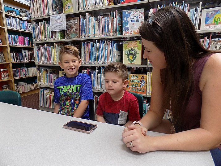 """Cassie Durbin, right, and her sons Titus and Grayson use the Dial-A-Story feature to listen to """"The Town Mouse and the Country Mouse"""" at the Chino Valley Public Library on Wednesday, July 7, 2021. Durbin and her sons are regulars at the library but are recent users of the Dial A Story feature and are pretty excited about it. (Rebecca Laurence/Courtesy)"""