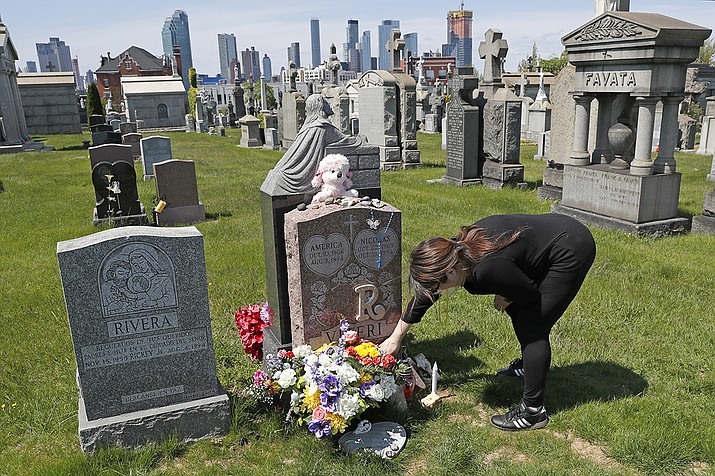 In this Sunday, May 10, 2020 file photo, Sharon Rivera adjusts flowers and other items left at the grave of her daughter, Victoria, who died of a drug overdose in Sept. 22, 2019, when she just 21 years old.  (Kathy Willens, AP File)