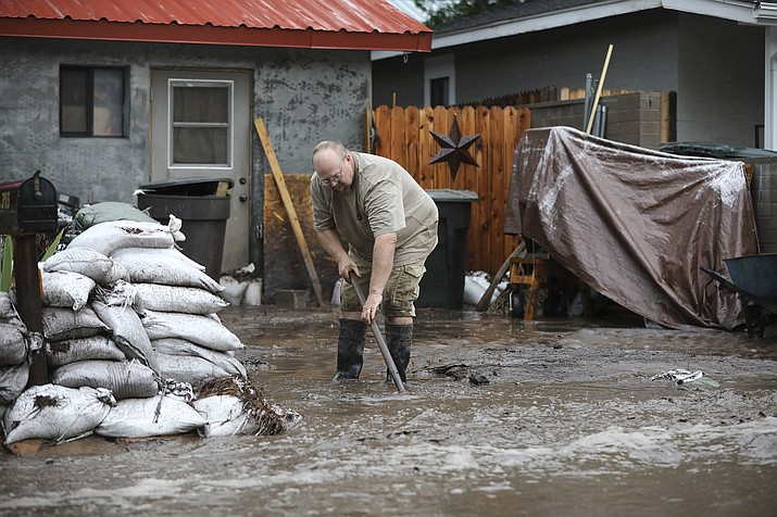 A resident shovels back floodwater as monsoon rains fell on the Museum Fire burn area causing flooding from the Paradise Wash in east Flagstaff on Wednesday, July 14, 2021. The threat of flash flooding will remain through next week, the National Weather Service said, though the coverage will be more scattered than widespread. (Jake Bacon/Arizona Daily Sun via AP)