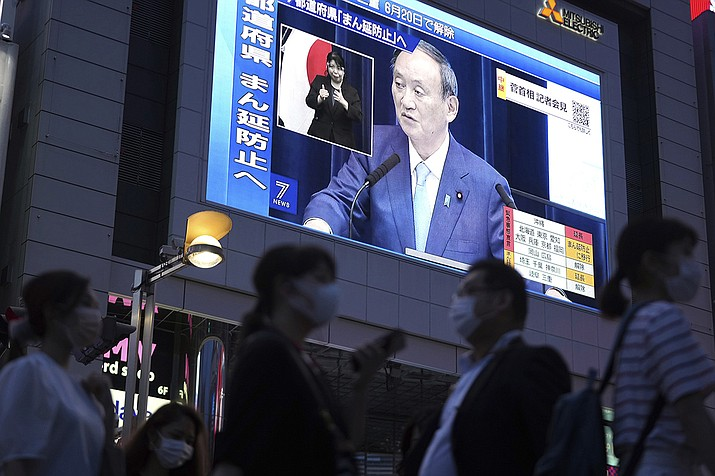 In this June 17, 2021 photo, people walk past a big screen as Japanese Prime Minister Yoshihide Suga holds a news conference in a live broadcasting on the current state of Japan's response to the coronavirus, in Tokyo. U.S. President Joe Biden, his Chinese counterpart Xi Jinping, Japanese Prime Minister Yoshihide Suga and Russian President Vladimir Putin are among Pacific Rim leaders gathering for a virtual meeting on Friday, July 16, 2021, to discuss strategies to help economies rebound from a resurgent COVID-19 pandemic. (Eugene Hoshiko, AP File)