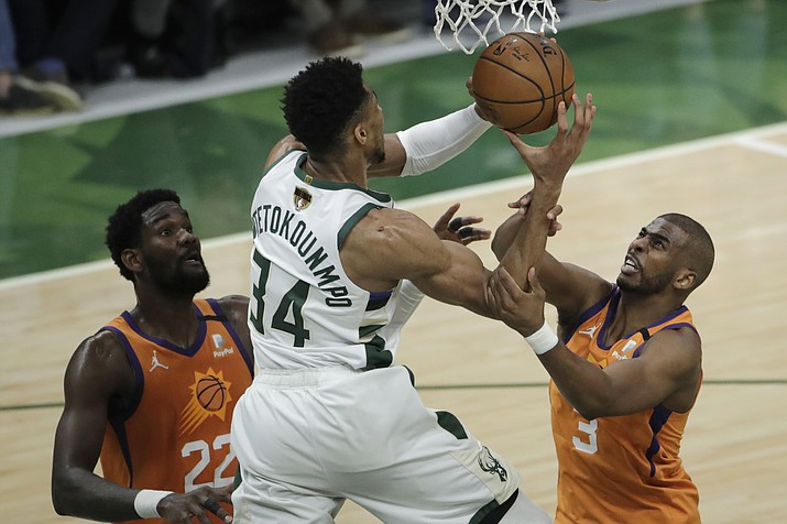 Milwaukee Bucks forward Giannis Antetokounmpo (34) drives to the basket between Phoenix Suns center Deandre Ayton (22) and guard Chris Paul (3) during the second half of Game 4 of basketball's NBA Finals Wednesday, July 14, 2021, in Milwaukee. (Aaron Gash/AP)