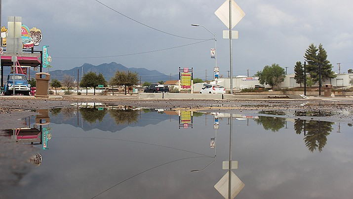 Water gathers along Andy Devine Avenue in Kingman after a recent storm. The forecast by the National Weather Service for Kingman calls for a chance of rain every day through the next week. (Photo by Travis Rains/Kingman Miner)
