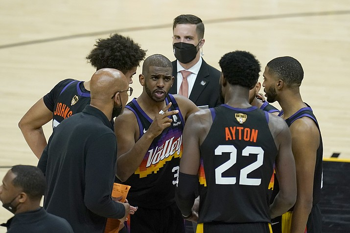 Phoenix Suns guard Chris Paul, middle, huddles with head coach Monty Williams, bottom left, center Deandre Ayton (22) and teammates during the second half of Game 5 of the NBA Finals against the Milwaukee Bucks, Saturday, July 17, 2021, in Phoenix. (Ross D. Franklin/AP)