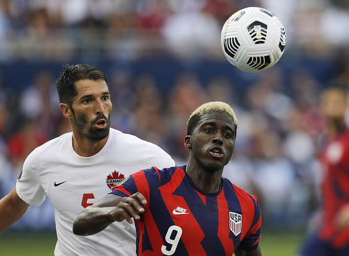 Canada defender Steven Vitoria (5) and U.S. forward Gyasi Zardes (9) chase down the ball during the second half of a CONCACAF Gold Cup soccer match in Kansas City, Kan., Sunday, July 18, 2021. (Colin E. Braley/AP)
