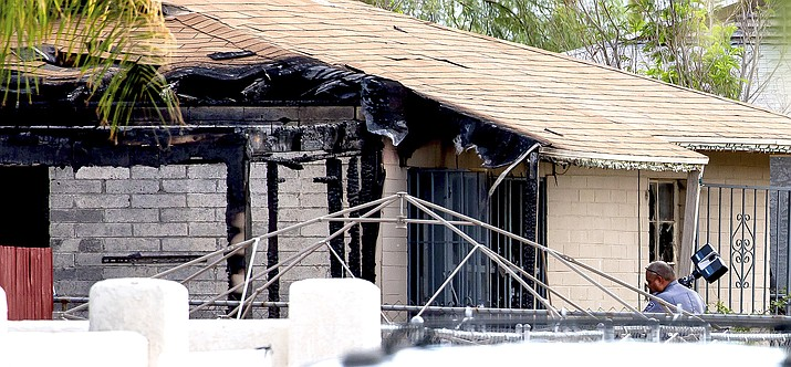 Tucson Police investigators work at the scene of a house fire where a body was found in Tucson, Arizona July 19, 2021. A gunman killed one person and wounded several others, including firefighters and paramedics, at the scene of a house fire in Arizona July 18 before being shot by an officer, authorities said. (Rebecca Sasnett/Arizona Daily Star via AP)