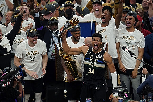 Milwaukee Bucks forward Giannis Antetokounmpo (34) reads with the championship trophy after defeating the Phoenix Suns in Game 6 of basketball's NBA Finals in Milwaukee, Tuesday, July 20, 2021. The Bucks won 105-98. (Paul Sancya/AP)