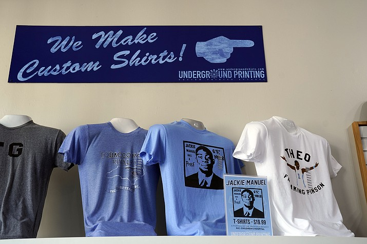 """Tee-shirts showing a likeness of former North Carolina basketball players Theo Pinson and Jackie Manuel are seen for sale at Underground Printing in Chapel Hill, N.C., Thursday, July 15, 2021. The Ann Arbor-based company Underground Printing is positioned to help athletes and its business make money with merchandise it can sell online. """"It's the same service that students and groups and departments use anyway so this is just an avenue for athletes to do the same thing,"""" said owner Rishi Narayan, whose company has 25 stores from Chapel Hill to Norman, Oklahoma. (Gerry Broome/AP)"""