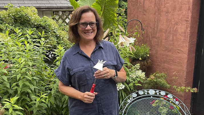 """Elizabeth Licata, moderator of the Facebook group, WNY Gardeners, poses for a photograph on July 8, 2021 in Buffalo, N.Y. Moderating a Facebook gardening group is not without challenges. Facebook's algorithms sometimes flag the word """"hoe"""" as """"violating community standards,"""" apparently referring to a different word. (Elizabeth Licata via AP)"""