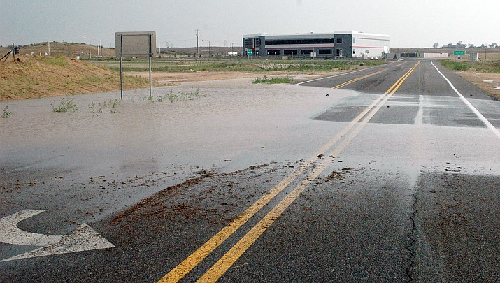 Runoff from the Sunday, July 11, 2021, storm that hit the Prescott area makes its way across a road near the airport and the Deep Well Ranch roundabout. (Tim Wiederaenders/Courier)